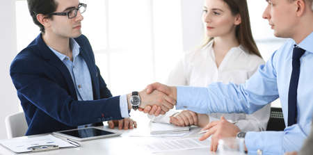 Business people shaking hands at meeting or negotiation. Group of businessmen and women in modern office. Teamwork, partnership and handshake concept Stockfoto