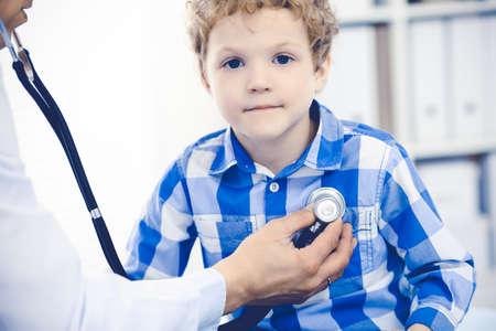 Arzt und geduldiges Kind. Arzt untersucht kleinen Jungen. Regelmäßiger Arztbesuch in der Klinik. Medizin- und Gesundheitskonzept