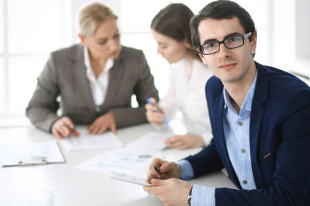 Group of business people discussing questions at meeting in modern office. Headshot of businessman at negotiation. Teamwork, partnership and business concept