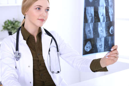 Doctor woman examining x-ray picture near window in hospital. Surgeon or orthopedist at work. Medicine and healthcare concept. Khaki colored blouse of a therapist looks good