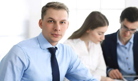 Group of business people discussing questions at meeting in modern office. Headshot of businessman at negotiation. Teamwork, partnership and business concept Imagens