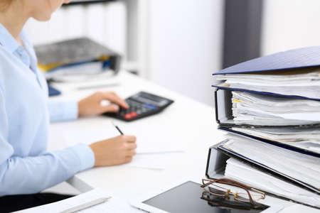 Las carpetas con papeles están a la espera de ser procesadas por una mujer de negocios o un contable en forma borrosa. Concepto fiscal y de auditoría interna