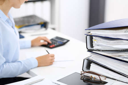 Segregatory z papierami czekają na przetworzenie przez kobietę biznesu lub księgowego z powrotem w rozmyciu. Audyt wewnętrzny i koncepcja podatkowa