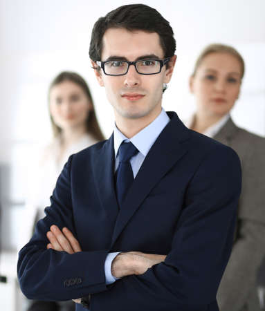 Headshot of businessman standing straight with colleagues at background in office. Group of business people discussing questions at conference or presentation. Success and business concept