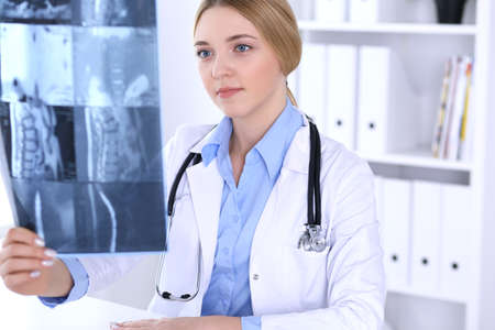 Doctor woman examining x-ray picture near window in hospital. Surgeon or orthopedist at work. Medicine and healthcare concept. Blue colored blouse of a therapist looks good Imagens