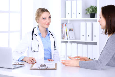 Young woman doctor and patient at medical examination at hospital office. Blue color blouse of therapist looks good. Medicine and healthcare concept