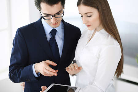 Businessmen and woman using tablet computer in modern office. Colleagues or company managers at workplace. Partners discussing contract. Business concept Imagens