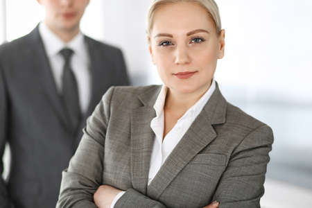 Business woman standing straight with colleague businessman in office, headshot. Success and corporate partnership concept Imagens