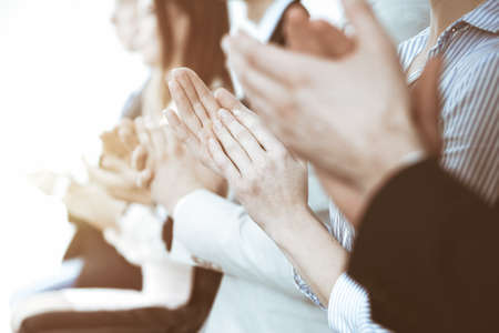 Business people clapping and applause at meeting or conference, close-up of hands. Group of unknown businessmen and women in modern white office. Success teamwork or corporate coaching concept. Imagens