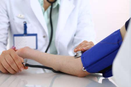 Onbekende artsenvrouw die bloeddruk van vrouwelijke patiënt controleert, close-up. Cardiologie in geneeskunde en gezondheidszorgconcept