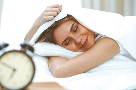 Beautiful young and happy woman sleeping while lying in bed comfortably and blissfully smiling Stock Photo