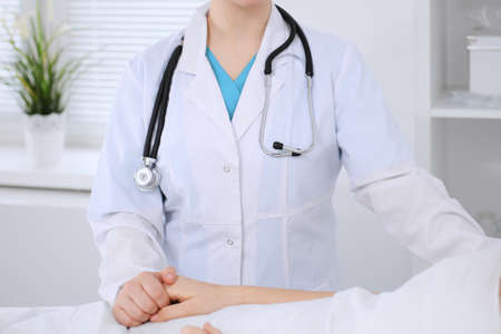 Female doctor holding application form while consulting patient.