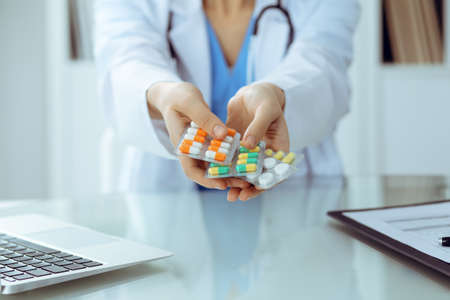 Female doctor hand holding pack of different tablet blisters closeup. Life save service, legal drug store, prescribe medicament, blood pressure, disease healing concept 写真素材