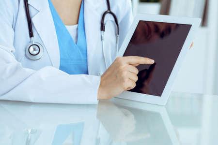 Ärztin mit Tablet-Computer beim Sitzen am Arbeitsplatz, Nahaufnahme der Hände. Konzept für Medizin, Gesundheitswesen und Hilfe.
