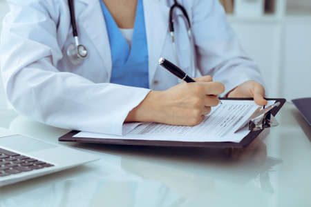 Doctor woman filling up medical form while sitting at the table, close-up of hands. Stockfoto