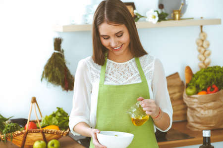 Young happy woman cooking in the kitchen. Healthy meal, lifestyle and culinary concepts. Good morning begins with fresh salad Stock Photo