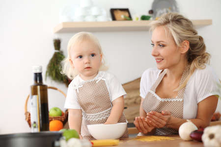 Happy mother and little daughter cooking in kitchen. Spending time all together, family fun concept