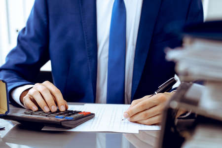 Bookkeeper or financial inspector hands making report, calculating or checking balance. Internal Revenue Service inspector man checking financial document. Business, tax and audit concepts Stockfoto