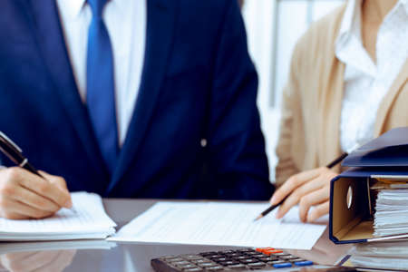 Comptable ou inspecteur financier et secrétaire faisant un rapport, calculant ou vérifiant le solde. Inspecteur de l'Internal Revenue Service vérifiant le document financier. Concepts commerciaux, fiscaux et d'audit
