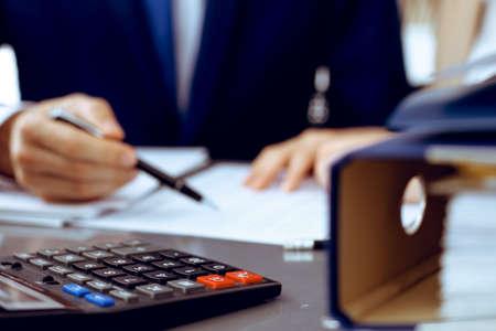 Reliures avec des papiers en attente de traitement avec un homme d'affaires ou un comptable de retour dans le flou. Budget de planification comptable. Audit, assurance et concept d'entreprise Banque d'images