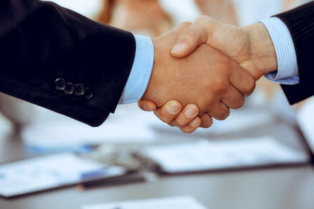 Business people shaking hands at meeting while theirs colleagues clapping and applauding. Group of unknown businessmen and women in modern white office. Success teamwork, partnership and handshake concept