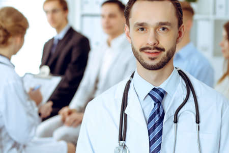 Doctor smiling against of group of patients and nurse. Best treatment and service in medicine. Health care concept Stockfoto