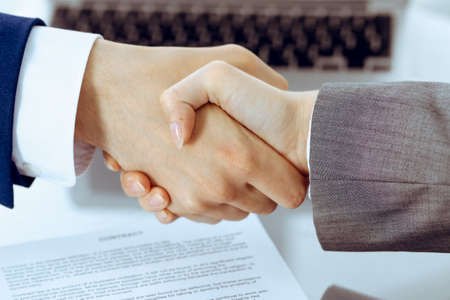 Businessman and business woman shaking hands to each other above signed contract. Success at negotiation and agreement concept