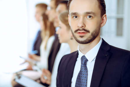 Businessman headshot against a group of business people at a meeting or negotiation in office