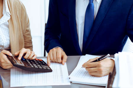 Bookkeeper or financial inspector and secretary making report, calculating or checking balance. Internal Revenue Service inspector checking financial document. Business, tax and audit concepts