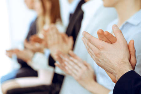 Business people clapping and applause at meeting or conference, close-up of hands. Group of unknown businessmen and women in modern white office. Success teamwork or corporate coaching concept.