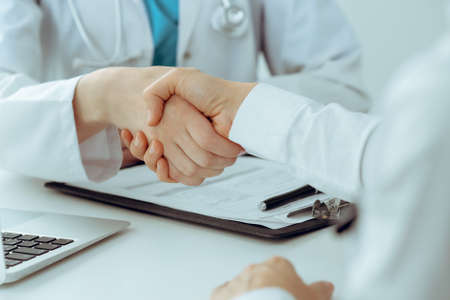 Doctor and patient shaking hands, close-up. Medicine, healthcare and trust concept Stockfoto