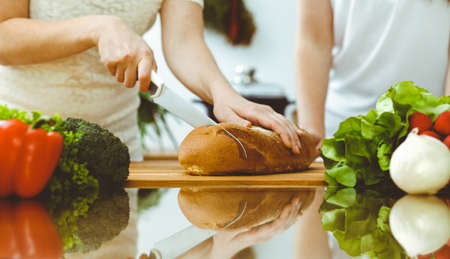 Closeup of human hands cooking in kitchen. Mother and daughter or two female friends cutting bread for dinner. Friendship, family and lifestyle concepts Stockfoto