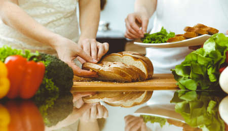 Closeup of human hands cooking in kitchen. Mother and daughter or two female friends cutting bread for dinner. Friendship, family and lifestyle concepts Stock Photo