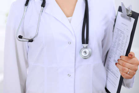 Stethoscope at female doctor breast at hospital office. Unknown physicians hands close-up. Medicine and health care concept