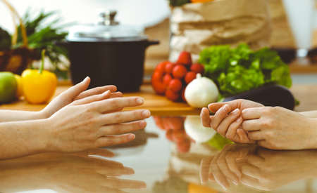 Closeup of human hands discussing something while cooking in kitchen. Women talking about menu. Family dinner, friendship and lifestyle concept Stockfoto