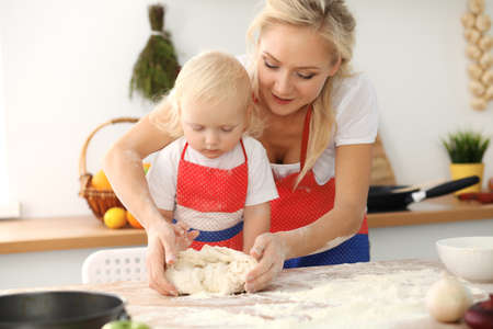 Little girl and her blonde mom in red aprons playing and laughing while kneading the dough in kitchen. Homemade pastry for bread, pizza or bake cookies. Family fun and cooking concept Stockfoto