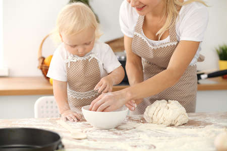 Little girl and her blonde mom in beige aprons playing and laughing while kneading the dough in kitchen. Homemade pastry for bread, pizza or bake cookies. Family fun and cooking concept