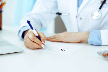 Female doctor filling up prescription form while sitting at the desk in hospital closeup. Healthcare, insurance and excellent service in medicine concept Stockfoto
