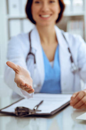 Closeup of medicine doctor offering helping hand or handshake. Partnership and trust concept Imagens