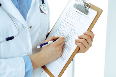 Female doctor using medical form on clipboard closeup. Physicianat work in hospital or clinic. Healthcare, insurance and medicine concept