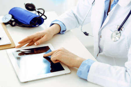 Doctor working table. Woman physician using tablet computer while sitting in hospital office close-up. Healthcare, insurance and medicine concept Stok Fotoğraf