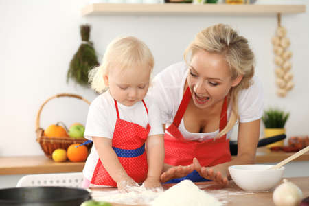 Little girl and her blonde mom in red aprons playing and laughing while kneading the dough in kitchen. Homemade pastry for bread, pizza or bake cookies. Family fun and cooking concept Stok Fotoğraf