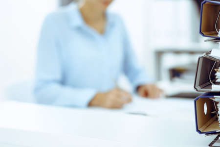 Binders with papers are waiting to be processed by business woman or bookkeeper back in blur. Internal Audit and tax concept Foto de archivo - 129482937