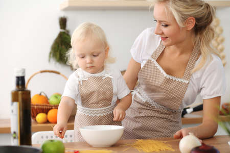 Happy mother and little daughter cooking in kitchen. Spending time all together, family fun concept Foto de archivo - 129482933