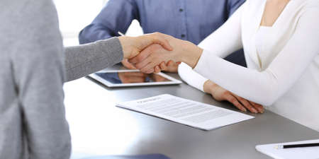 Group of business people shaking hands after discussing questions and achieving agreement at meeting in modern office. Handshake close-up. Teamwork, partnership and business concept.