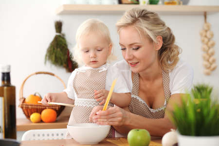 Happy mother and little daughter cooking in kitchen. Spending time all together, family fun concept Foto de archivo - 129482936