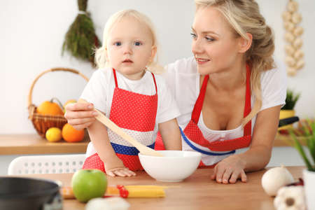 Happy mother and little daughter cooking in kitchen. Spending time all together, family fun concept Foto de archivo - 129482938