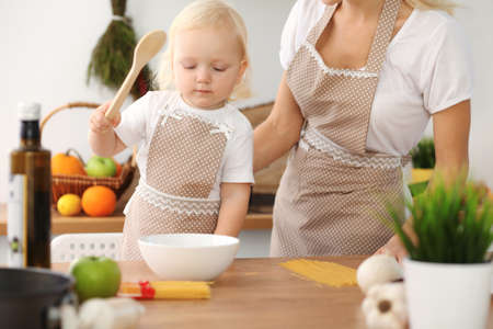 Happy mother and little daughter cooking in kitchen. Spending time all together, family fun concept Foto de archivo - 129482943