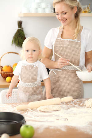 Little girl and her blonde mom in beige aprons playing and laughing while kneading the dough in kitchen. Homemade pastry for bread, pizza or bake cookies. Family fun and cooking concept Foto de archivo - 129482944