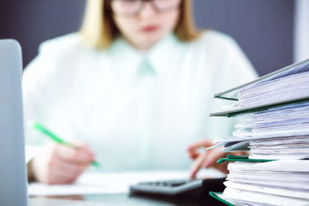 Bookkeeper or financial inspector making report, calculating or checking balance. Audit and tax service concept. Green colored image background. Banco de Imagens